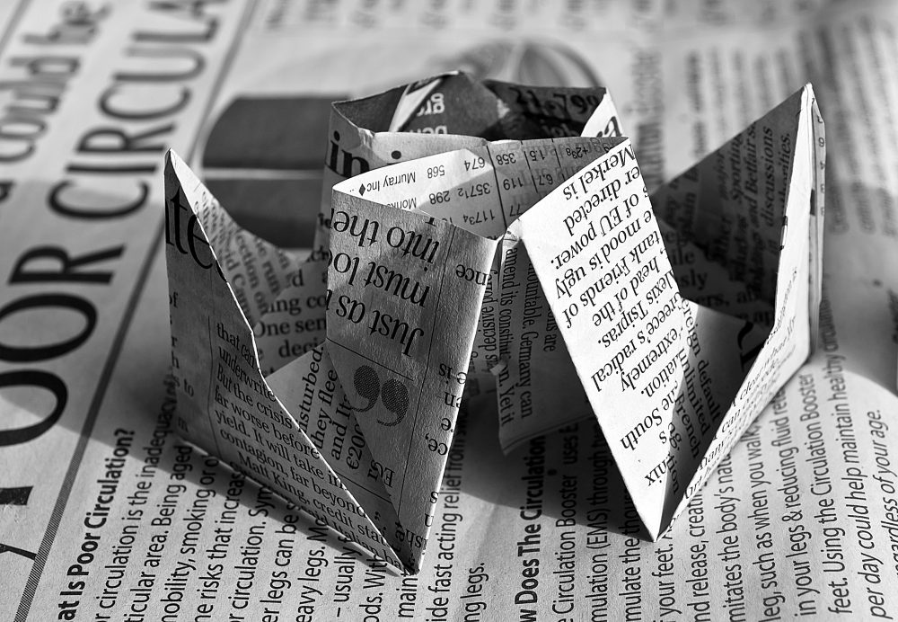 Newspapers are useful for a variety of reasons; here, a newsprint cootie catcher sits on top of a daily paper.