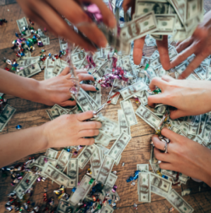 Pairs of hands reaching out to grab money on a table