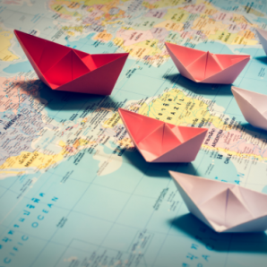Red paper boat on map leads lighter colored ones