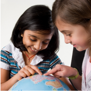Two girls of different cultural backgrounds playing with globe